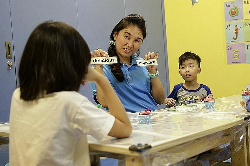 Learning Journey Education Centre founder Grace Tan shows six-year-olds how to craft sentences during a class activity. The centre conducts Primary 1 preparation programmes during the holidays.