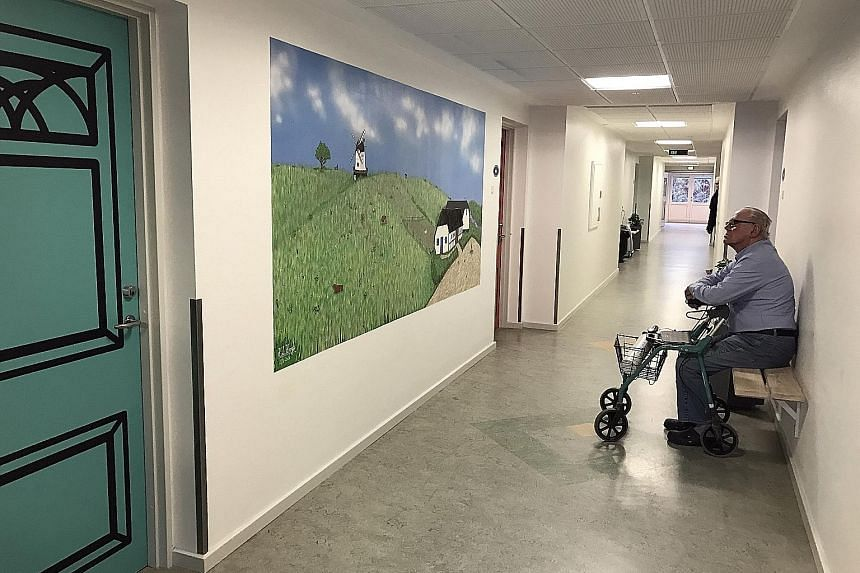 This painting that dementia patient Hans H. Hansen, 88, is looking at is one of the paintings at Havebaek nursing home in Odense that help patients with dementia relax and reminisce.