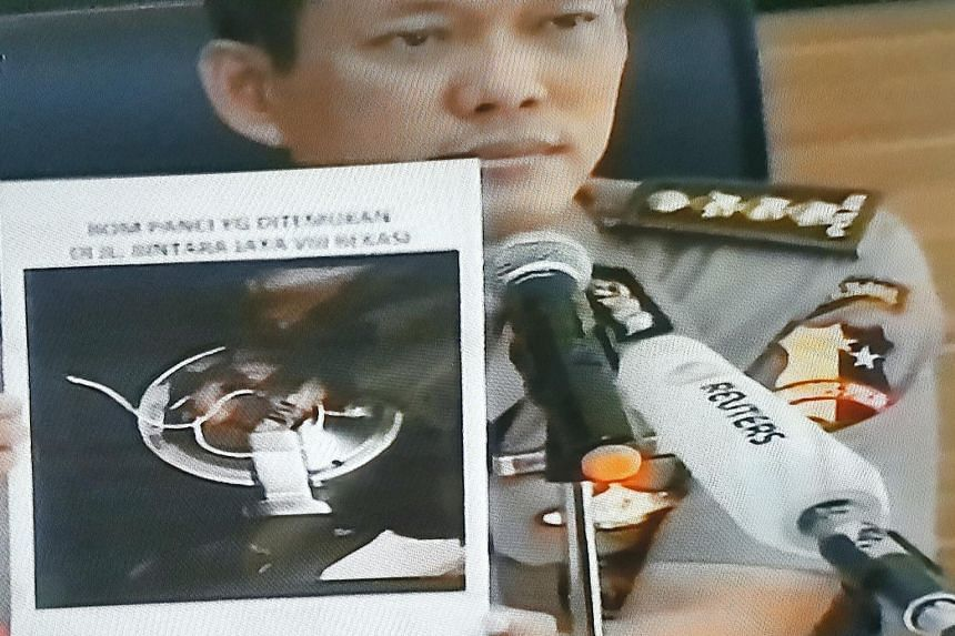 """Col Awi with a photo of the """"rice cooker"""" bomb. The police say it contained explosives more powerful than military-grade TNT and had a blast radius of about 300m."""