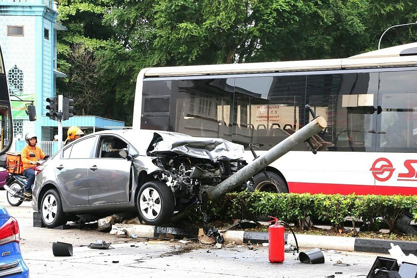 The grey sedan hit a traffic light, causing it to topple over.