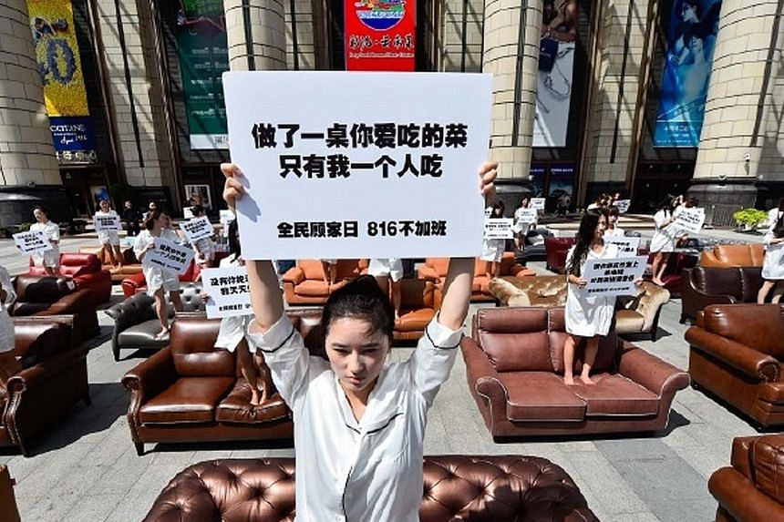 """A woman in Shanghai protesting against the impact of overtime work on families. The placard she is holding reads: """"Prepared a feast, but I'm the only one eating the food."""""""