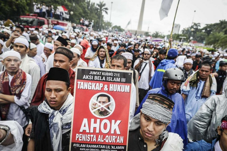 An Indonesian carries a placard 'arrest and prosecute Ahok' during a mass protest against allegedly blasphemous remark made by Jakarta's Governor Basuki Tjahaja Purnama, popularly known as Ahok, at the National Monument (Monas) in Jakarta, Indonesia,