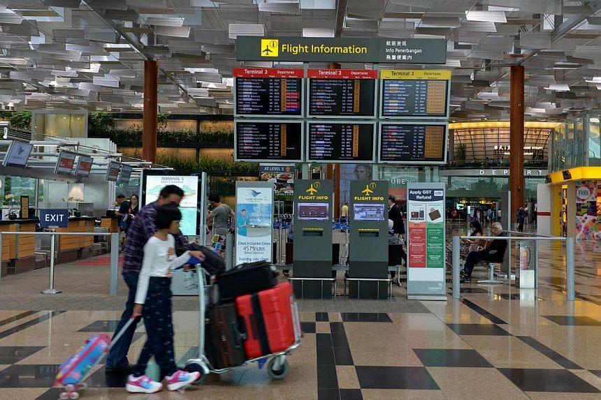 Travellers walking past the flight information display at Changi Airport Terminal 3.