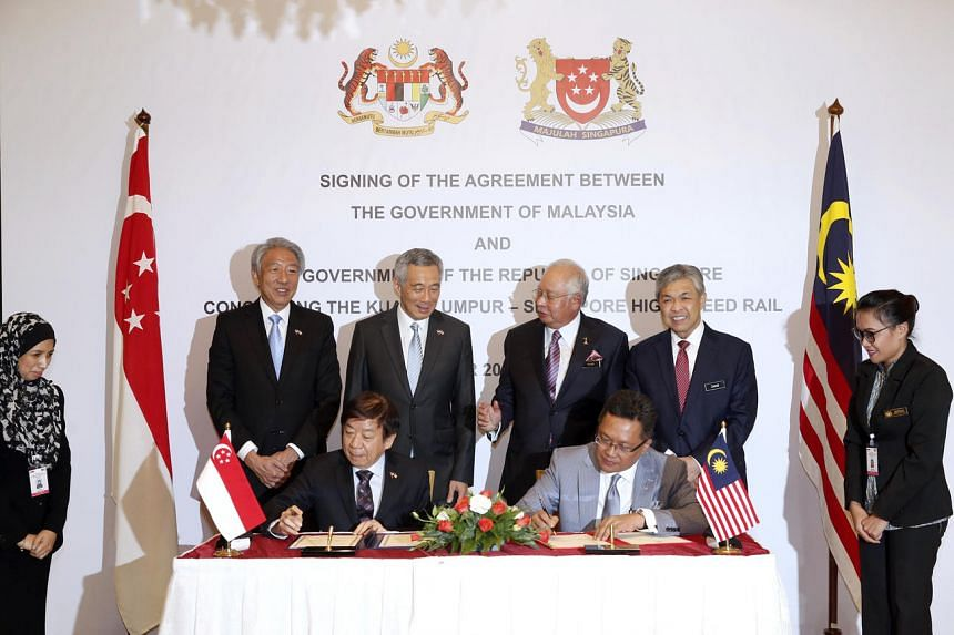 Coordinating Minister for Infrastructure and Transport Minister Khaw Boon Wan, and Malaysian Minister in the Prime Minister's Department Abdul Rahman Dahlan sign the bilateral agreement, with (from left) DPM Teo Chee Hean, PM Lee Hsien Loong, Malaysi