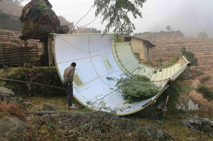 A man examining a piece of a Chinese-built Long March 3B rocket that landed in a field in Suichuan county, in China's central Jiangxi province, on Sunday. The rocket part fell to the earth following the successful launch of an FY-4 geostationary orbi