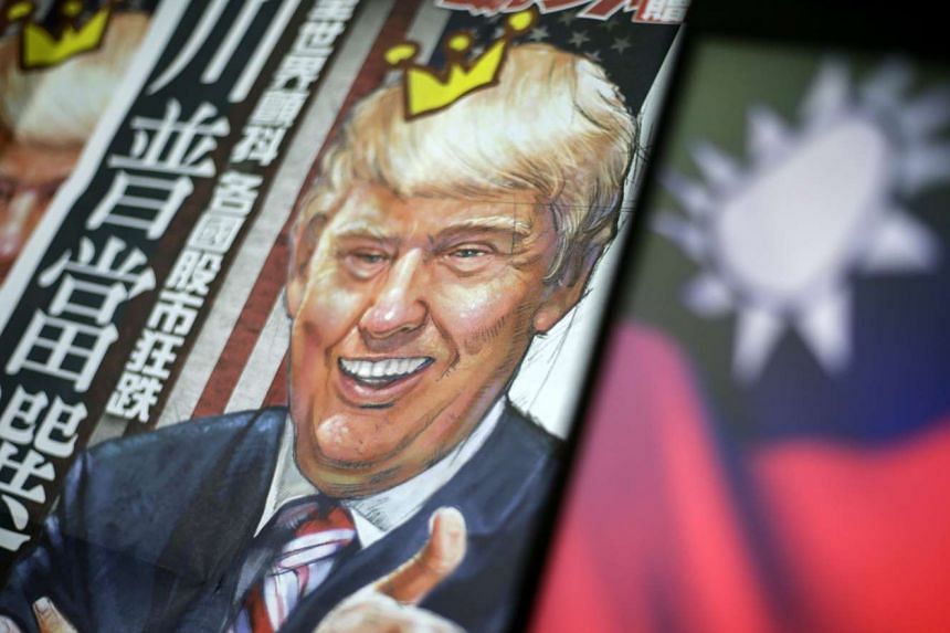 A newspaper headline with an illustration of US President-elect Donald Trump is pictured next to a Taiwanese flag, in Taipei on Dec 12, 2016.