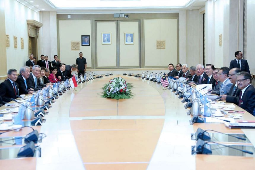 The Singaporean (left) and Malaysian delegations meet before the signing of the high-speed rail line bilateral agreement