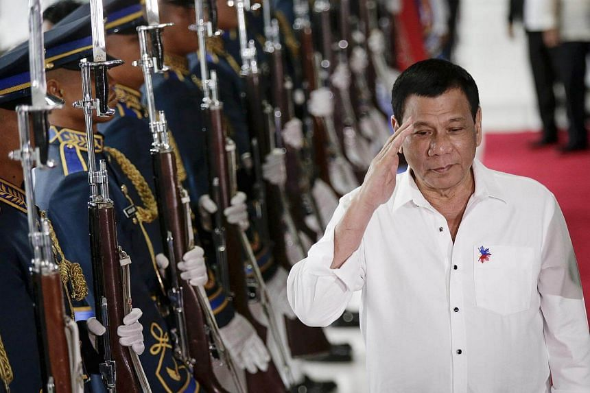 Philippine President Rodrigo Duterte reviewing honour guards during a departure ceremony at the Manila International Airport in Pasay City.