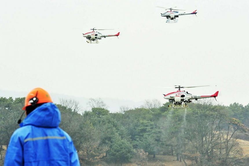 Unmanned aerial vehicles spray a disinfectant over a habitat for migratory birds in Icheon, east of Seoul, 14 Dec, 2016.
