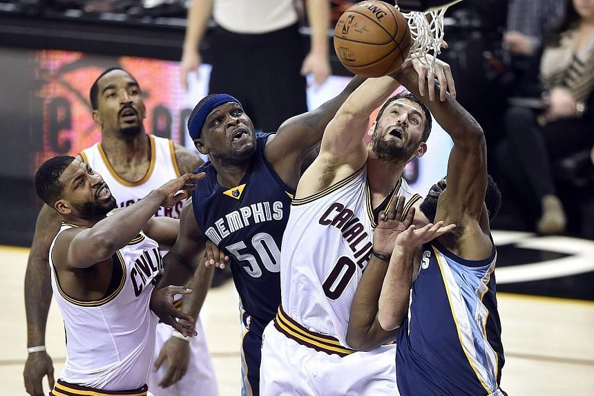 Grizzlies forward Zach Randolph (centre) reaches for a rebound between Cavaliers' Tristan Thompson (left) and Kevin Love (No. 0) at Quicken Loans Arena. Randolph scored 18 points and grabbed five rebounds in his first start this season but it was not