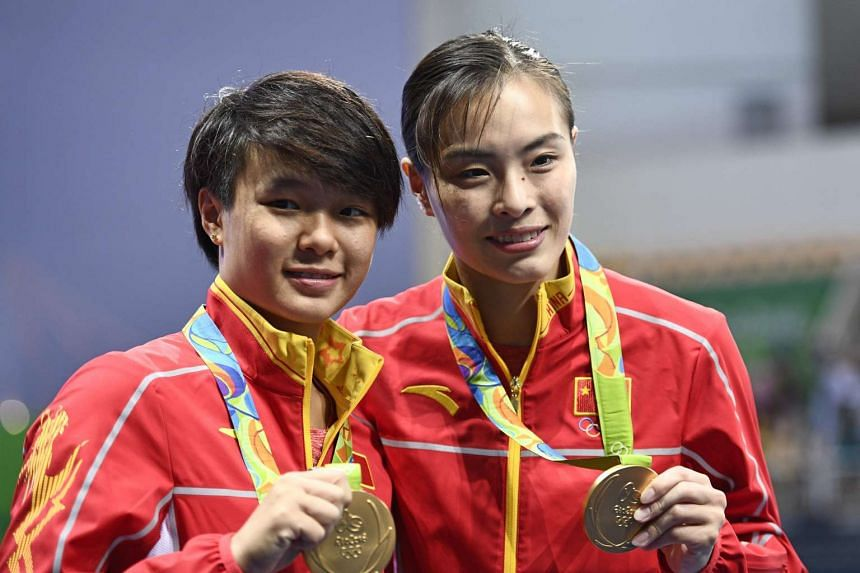 Gold medallists China's Wu Minxia (right) and Shi Tingmao pose during the podium ceremony of the Women's Synchronized 3m Springboard final event at the Rio 2016 Olympic Games at the Maria Lenk Aquatics Stadium in Rio de Janeiro on Aug 7, 2016.
