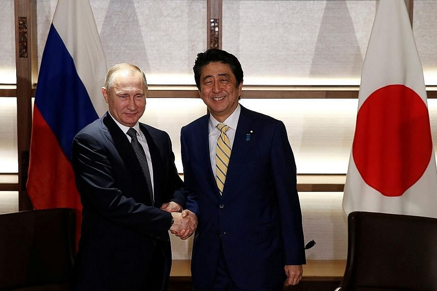 President Putin with Prime Minister Abe at the start of their summit in Nagato, Yamaguchi, yesterday. They ordered a start to talks on conditions for joint economic activity on the four islands.