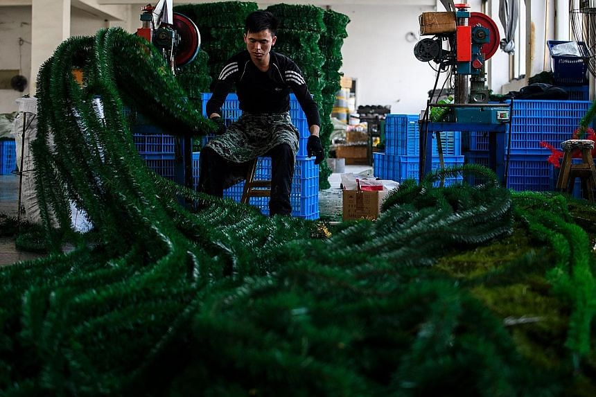 A worker cutting fake branches in a Christmas tree factory in Yiwu. While the factory exports 80 per cent of its output, domestic demand has doubled in five years.
