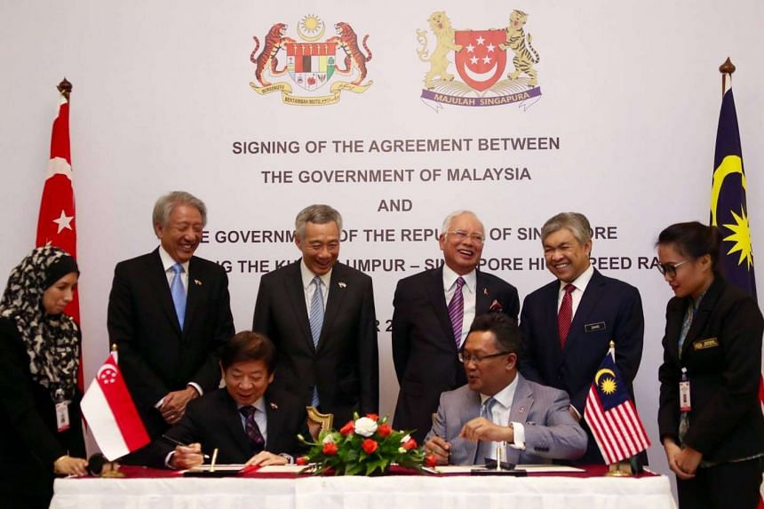 Prime Minister Lee Hsien Loong (centre left) and his Malaysian counterpart Najib Razak (centre right) witnessing the signing of the milestone Singapore-KL high-speed rail bilateral agreement.