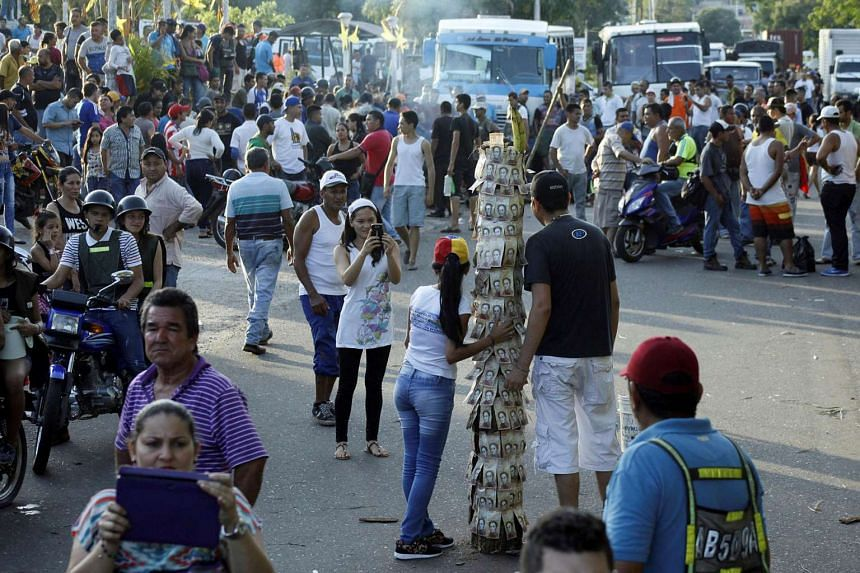 People taking pictures next to a pole covered with 100-bolivar bills during a protest in El Pinal, Venezuela, on Dec 16, 2016.