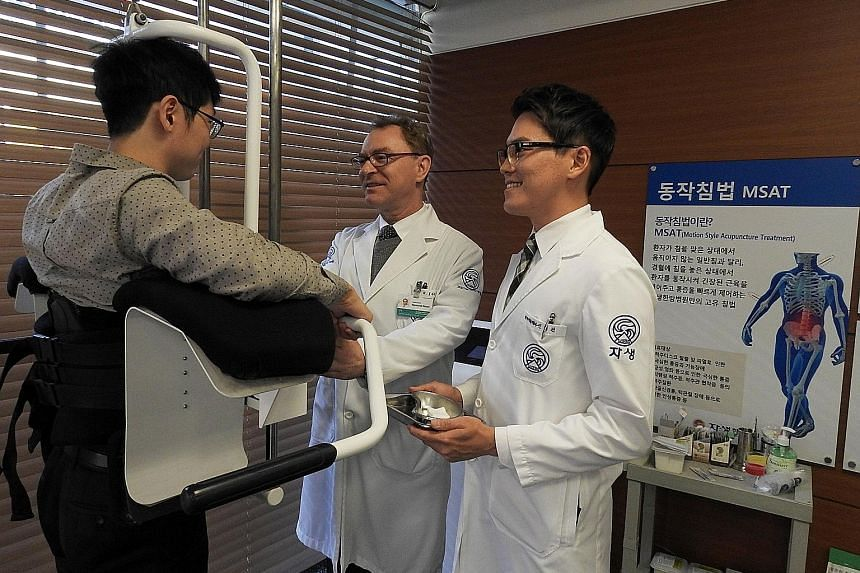 Dr Choi Woo Jung (left) says the Kwangdong Hospital of Traditional Korean Medicine draws 1,500 foreign patients a year. Korean traditional medicine includes the use of acupuncture which figure skater Kim Yuna (above, left) used to treat her back pain