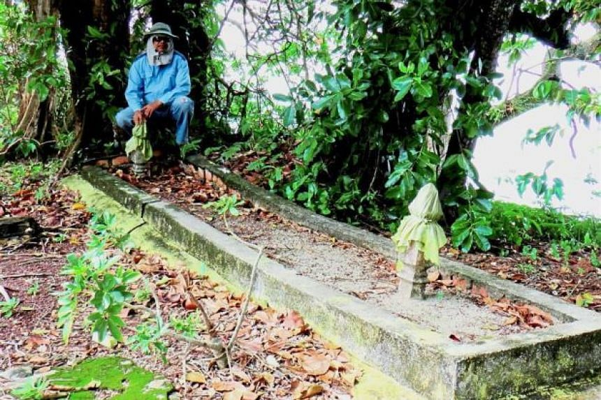 Mr Azman Wahab, assistant to historian Mohd Fuad Khusari M Said, at the large grave site in Pulau Upeh.