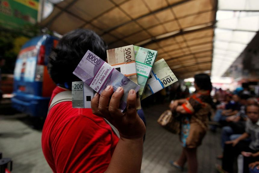 A woman holds newly designed rupiah notes after exchanging her old bills at a Bank Indonesia mobile bank in Jakarta on Dec 19, 2016