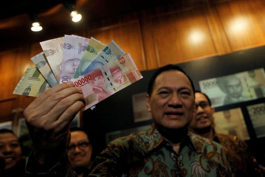 Bank Indonesia Governor Agus Martowardojo holding new rupiah notes at an official ceremony in Jakarta on Dec 19, 2016.