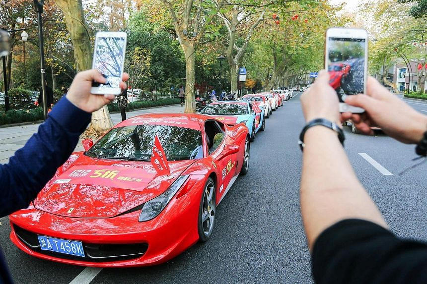 Passers-by taking photos of a Ferrari and other luxury cars covered with advertising banners on a street in Hangzhou, in China's eastern Zhejiang province, recently. The Beijing authorities are as much in a race to tighten capital controls as are Chi