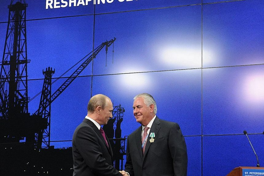 Above: Russia's President Putin (left) with Mr Tillerson at a June 2013 ceremony in St Petersburg to present awards to the heads and employees of major energy companies. Top: Mr Trump (centre), with his daughter Ivanka and Mr Friedman after their 201