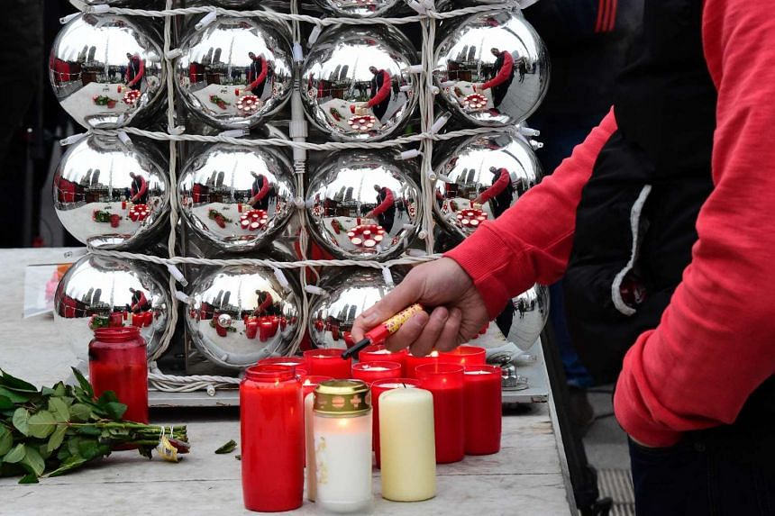 A man lighting a candle at a memorial for victims, at the site where a truck crashed into a Christmas market in Berlin, on Dec 20, 2016.