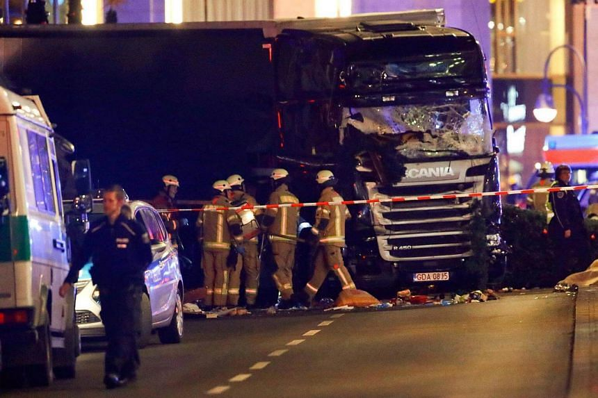 Police and emergency workers stand next to a crashed truck at the site of an accident at a Christmas market on Breitscheidplatz square in Berlin, Germany.