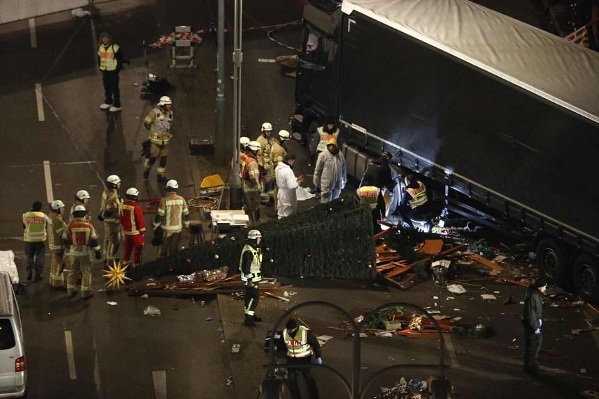Officials inspecting the scene after a truck crashed into a Christmas market in Berlin.