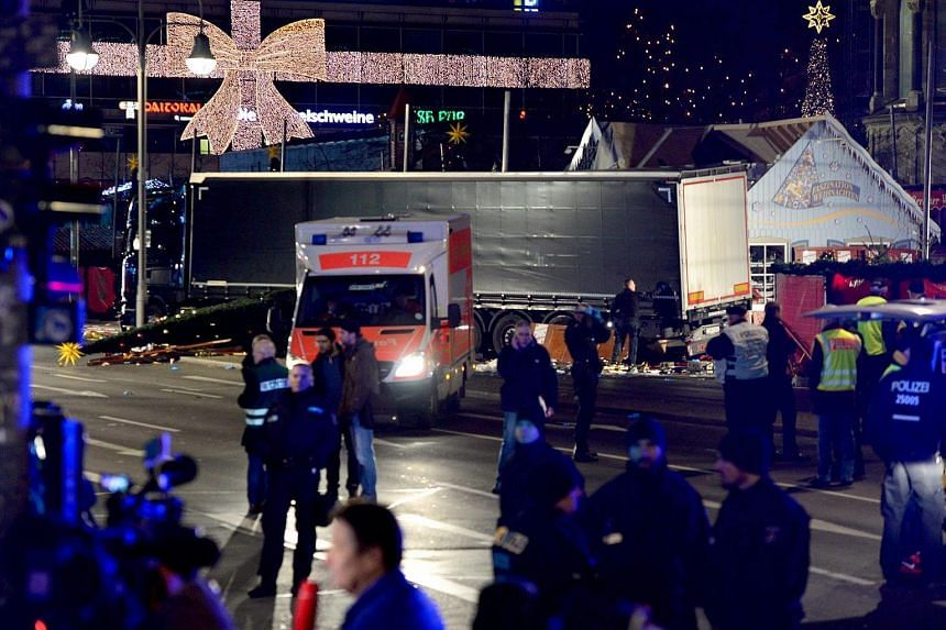 Police and rescue workers gather next to the truck after it crashed into a Christmas market.