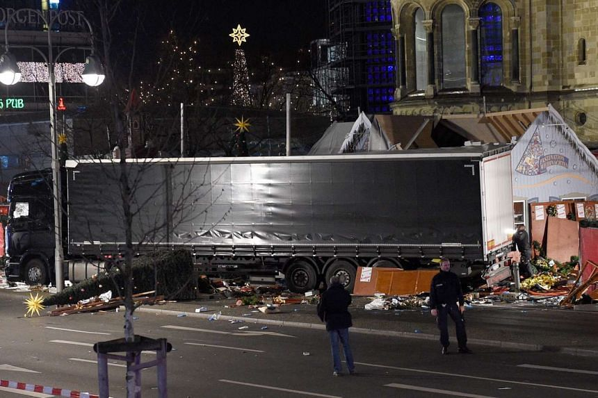 Policemen stand guard next to the truck that crashed into a Christmas market in Berlin.