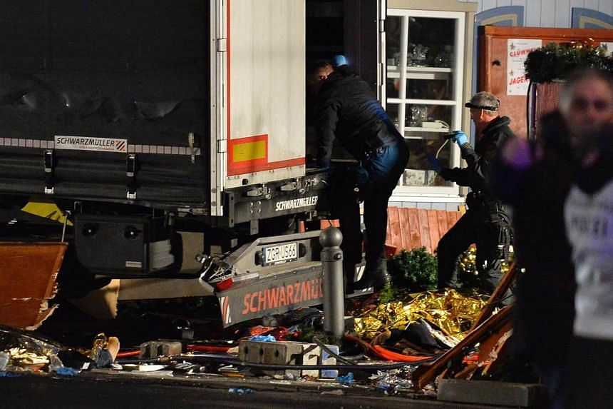 Policemen enter the truck that crashed into a Christmas market in Berlin.