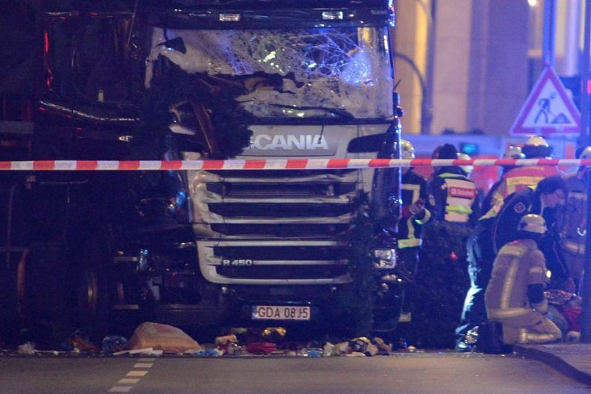 Rescue workers inspect the scenes and the truck that crashed into a Christmas market, close to the Kaiser Wilhelm memorial church in Berlin, Germany. According to the police, nine people are reported killed and many injured in what police suspect it