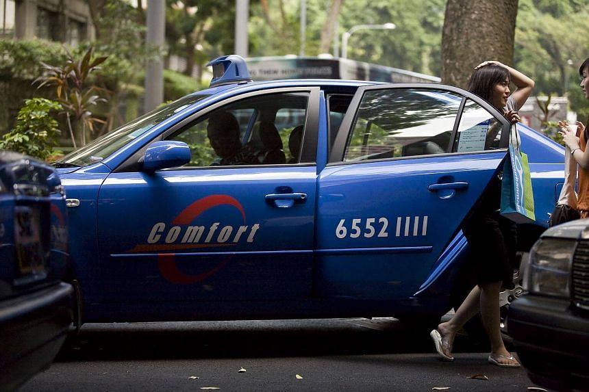 A passenger exits a ComfortDelgro Corp. taxi in Singapore.