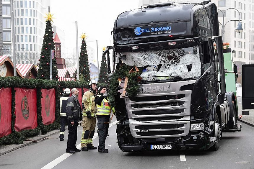 (Anti-clockwise from top): Policemen standing guard near the truck in Berlin on Monday night after it crashed into a Christmas market, killing 12 people; the truck being examined yesterday; and a woman praying yesterday near the scene of the attack,