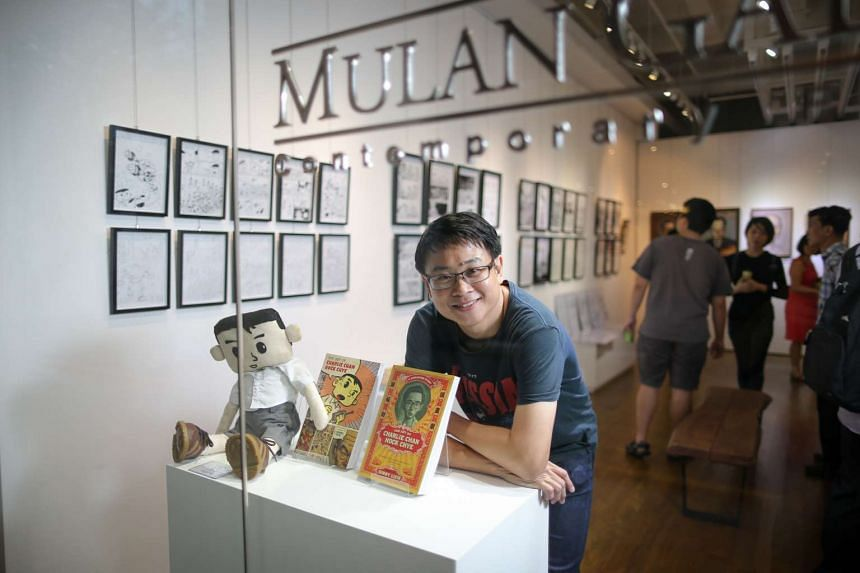 Graphic novelist Sonny Liew posing with two copies of his book The Art Of Charlie Chan Hock Chye.