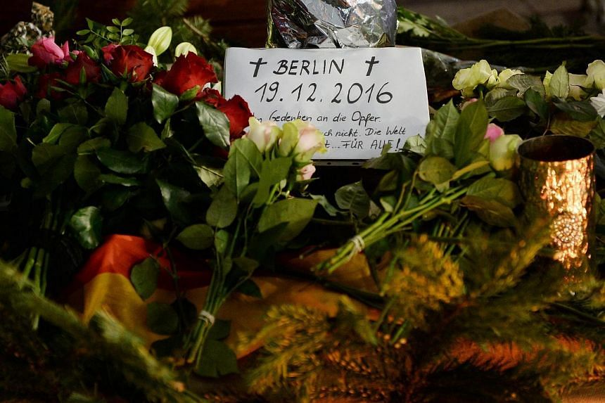 A note is placed among bunch of flowers to pay tribute to the victims at the site of the lorry attack in Berlin, Germany, on Dec 20, 2016.