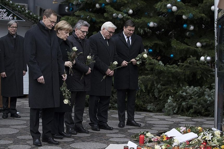 German Chancellor Angela Merkel on Tuesday looking at floral tributes near the scene of Monday's attack in Berlin. With her are (from left) Berlin Mayor Michael Mueller, German Interior Minister Thomas de Maiziere, German Foreign Minister Frank-Walte