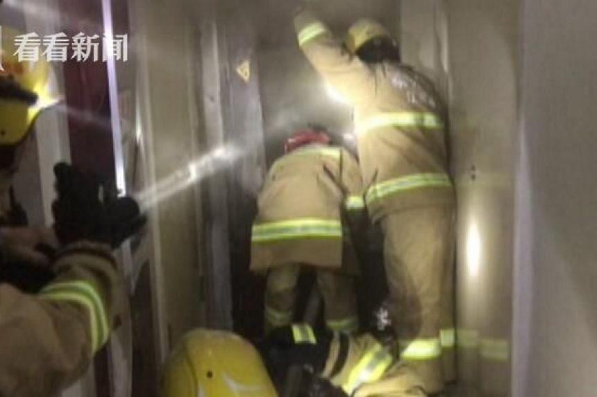 Firemen breaking down the door of the apartment on fire in Taizhou, Jiangsu province on Dec 20, 2016.