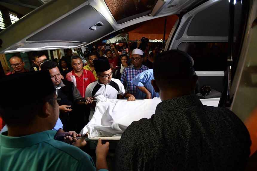 The bodies of the bus driver and his child being loaded onto the hearse in Muar, Malaysia, on Dec 24, 2016.