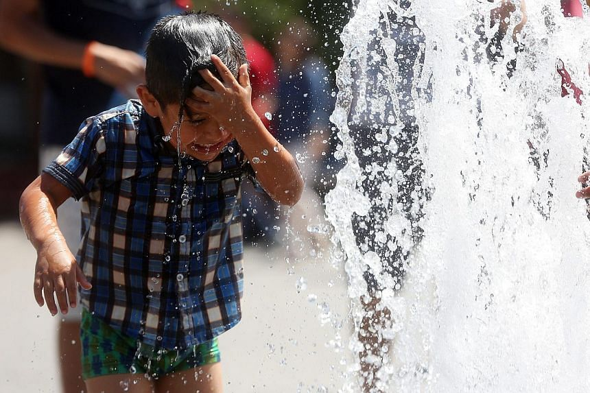 A boy cooling down at a water feature on a hot day at Buin Zoo, 30km south of Santiago, Chile, earlier this month. Wildfires raging through Alberta, Canada, earlier this year. Greenhouse gases that trap heat cause temperatures to rise, leading to ext