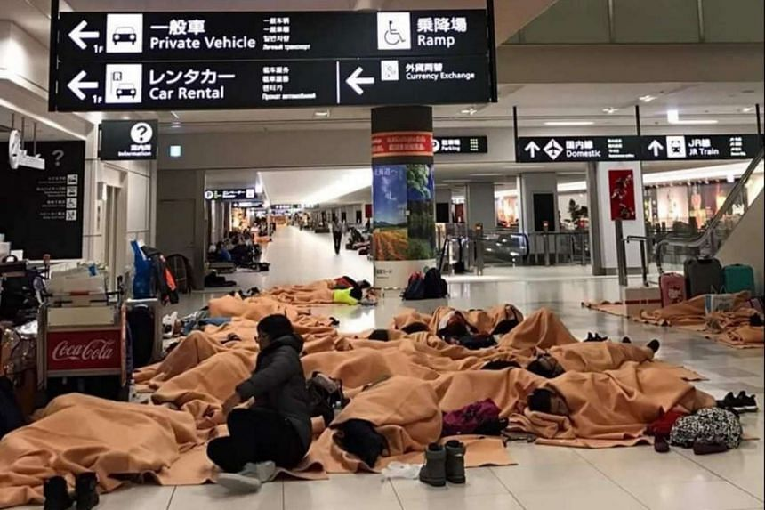 Stranded passengers sleep on the floor of New Chitose Airport in Sapporo on Friday (Dec 23).