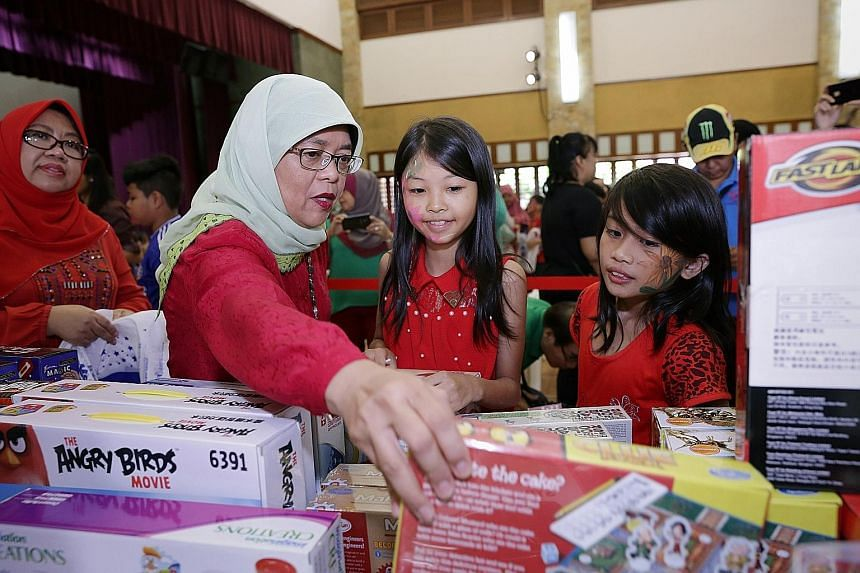 Madam Halimah helping Crystal Hoe, 10 (right), and Lim Yungfang, 11, choose their presents at yesterday's Toys Carnival @ Marsiling.