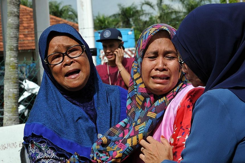 Madam Laila Kasdi (left), 62, mother of Ms Nor Saidatul Akmal Idris, and Madam Jamiah Saiman, 42, mother of Ms Nur Amira Izzaty Razip, at the Sultanah Fatimah hospital in Muar. Both their daughters died in the tragic crash. The Alisan Gold Coach bus,