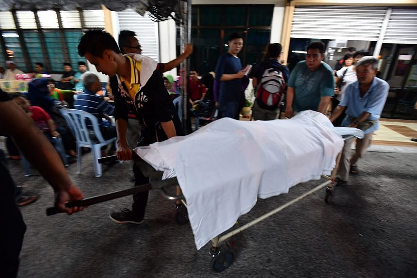 Relatives of Au Poi Kiew carry her body at the mortuary.