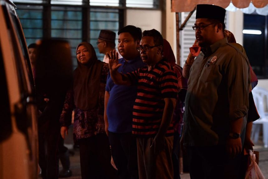 Relatives of Hamimah Mammu react after her body is placed in the hearse.