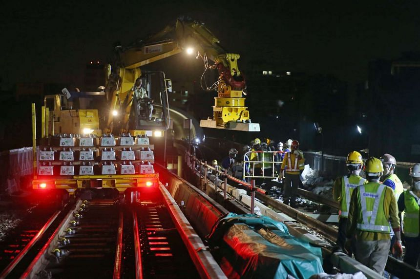 A road-rail vehicle placing a new concrete sleeper onto the track near Aljunied MRT station.