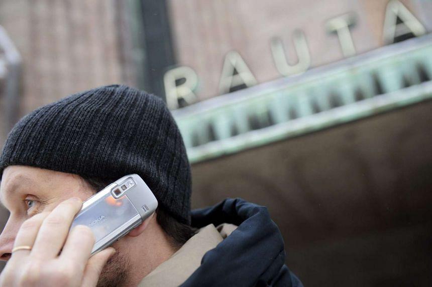 A man using a Nokia cellular phone outside Helsinki railway station.