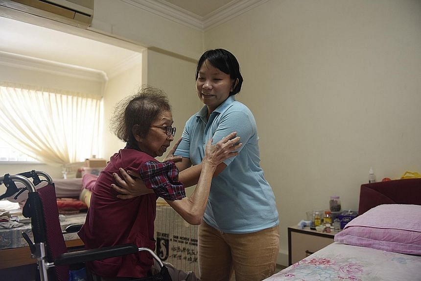 Myanmar live-in caregiver Than Than Sint helps Madam Tan Ah Sian, who has terminal gall bladder cancer, with daily activities like using the toilet.