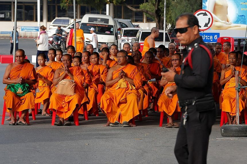 Monks praying on Tuesday at the gate of the Dhammakaya temple, whose abbot is the scandal-plagued Phra Dhammachayo.