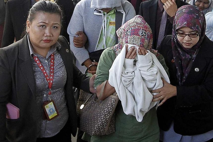 The accused (from front) Fauziah, Awang and Lim hiding their faces while being taken to court in Kota Kinabalu yesterday.